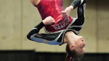 Denver gymnast, Claire Hammen, twists and soars on the beam. Photo by Gusto Kubiak.