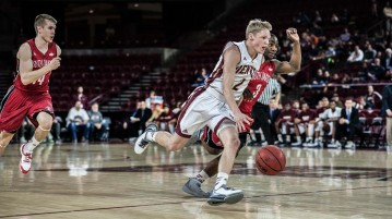 Freshman Joe Rosga (St. Paul, Minnesota) drives toward the basket during Denver's home game against the University of South Dakota. DU won the Summit League game  66-52. Photo by Gusto Kubiak.
