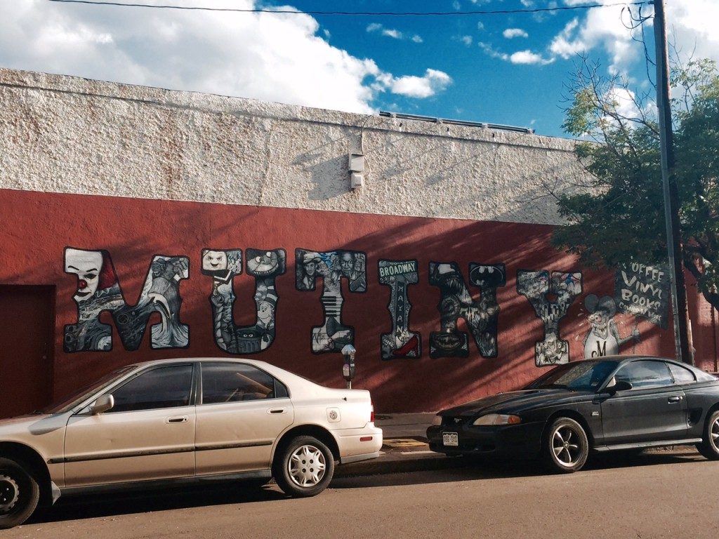 A hand-painted mural on the side of Mutiny Information Cafe. Photo by Meg McIntyre.